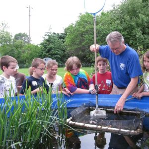 Dr. Dave showing students tadpoles